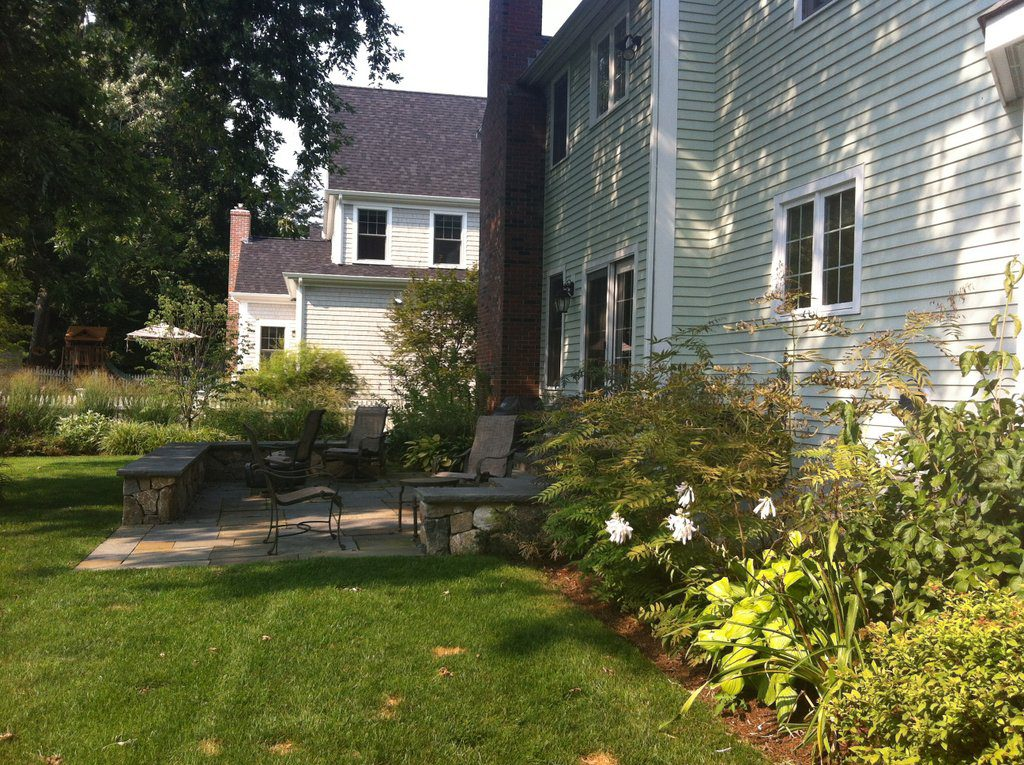 Patio replaces deck and bulkhead screened by plant material
